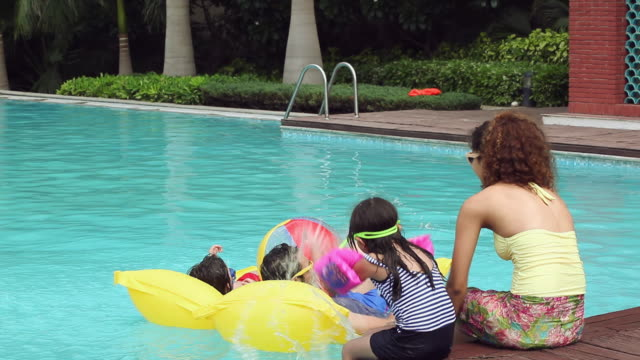 Family enjoying in the swimming pool, Delhi, India