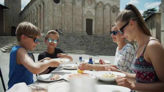 vidéos et rushes de famille appréciant le déjeuner un restaurant italien - italian culture