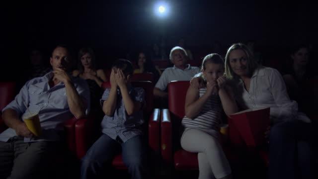 vídeos de stock, filmes e b-roll de family enjoying movie at the movie theater - mãos cobrindo olhos