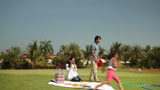 vidéos et rushes de family enjoying picnic in a park  - pelouse