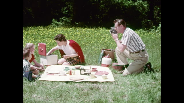 WS Family enjoying picnic in park, father filming children with Super 8mm camera / United States