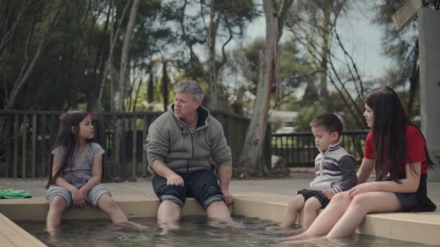 a family enjoying putting their feet in a thermal pool - thermal pool stock videos & royalty-free footage