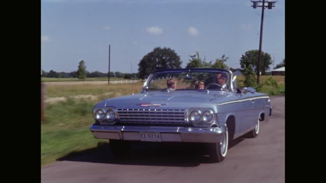 vidéos et rushes de ws pov family enjoying road trip, driving through farmland in convertible car / united states - 1950