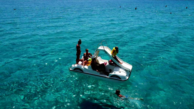 family enjoying swimming in a blue tropical sea - pedal boat stock videos and b-roll footage