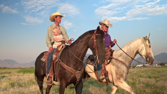 family enjoying the day horseback riding in the fields - rancher stock videos & royalty-free footage
