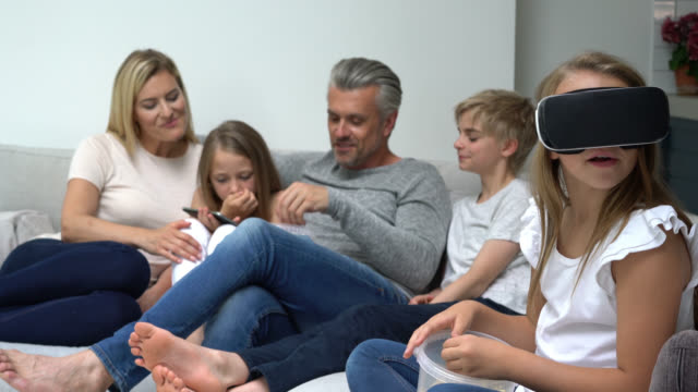 familie, die zeit auf dem sofa genießen, während mädchen einen film mit vr-brillen uhren - geschwister stock-videos und b-roll-filmmaterial