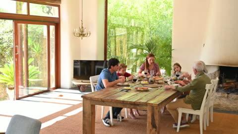 vídeos y material grabado en eventos de stock de familia disfrutando de la comida tradicional del mediodía y la conversación - mesa de comedor