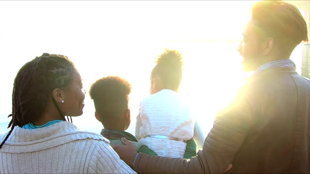 stockvideo's en b-roll-footage met familie genieten van uitzicht op de waterkant van de stad, dan lopen - mixed race person