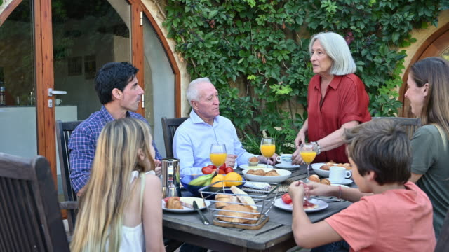 vídeos de stock e filmes b-roll de family enjoying weekend breakfast in outdoor courtyard - 40 44 anos