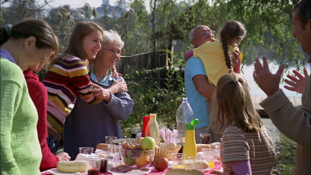 a family enjoys an outdoor barbecue. - nonno video stock e b–roll