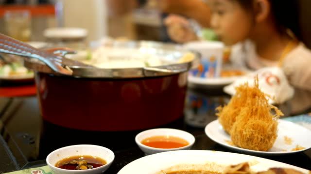 family enjoys eating sukiyaki - sukiyaki stock videos and b-roll footage