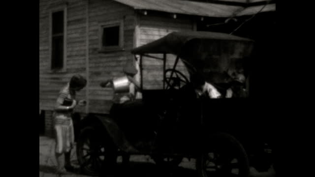 a family enjoys their model t ford on the farm fixes flat tire drives car - フォード・t型モデル点の映像素材/bロール