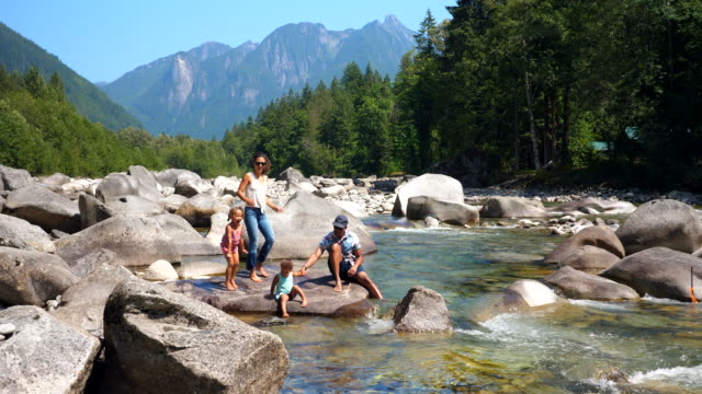 ws family exploring by river on summer afternoon - stone object stock videos & royalty-free footage