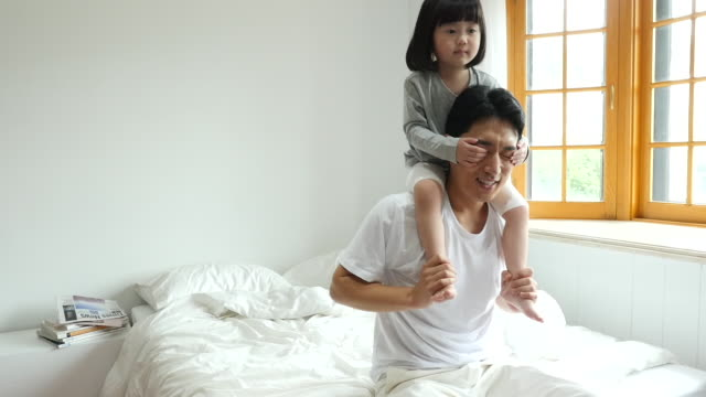 family - father carrying daughter on his shoulders and playing peekaboo together on the bed - peekaboo game stock videos & royalty-free footage
