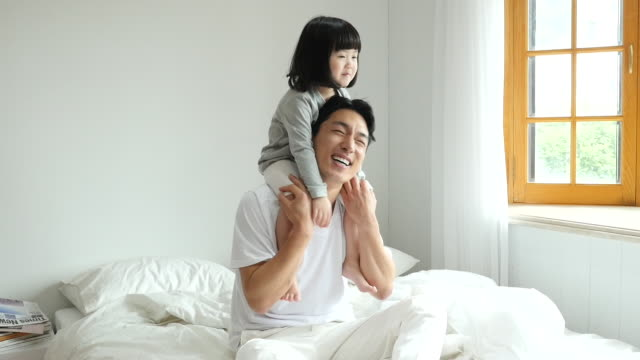 family - father carrying daughter on his shoulders and playing together on the bed - 肩に乗せる点の映像素材/bロール
