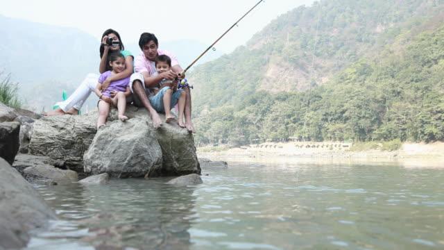 Family fishing at riverbank