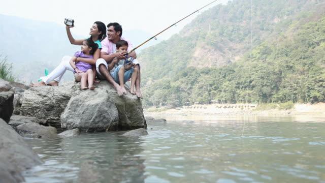 vídeos de stock e filmes b-roll de family fishing at riverbank  - geleira portátil