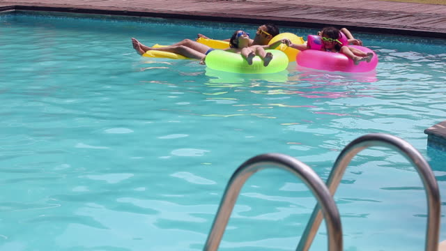 Family floating on inflatable bed in the swimming pool, Delhi, India