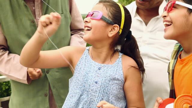 Family flying kite, Delhi, India