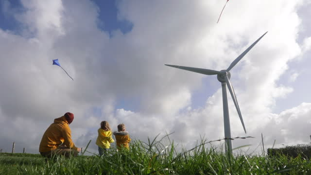 family flying kites by wind turbine - family with two children stock videos & royalty-free footage