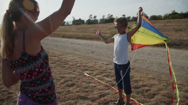 familienfliegendrachen an einem sonnigen sommertag - sonnig stock-videos und b-roll-filmmaterial