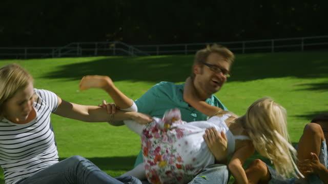fooling in famiglia nel parco - fare il solletico video stock e b–roll