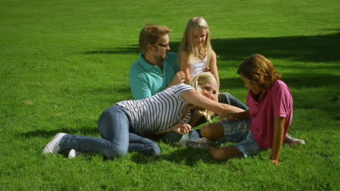 family fooling around in park - tickling stock videos & royalty-free footage
