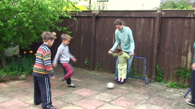 family football at the backyard - kicking stock videos & royalty-free footage