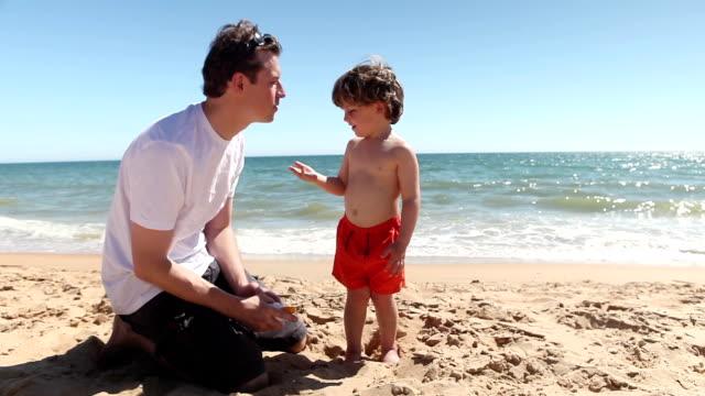 family fun applying sun cream – father and son - sun cream stock videos and b-roll footage
