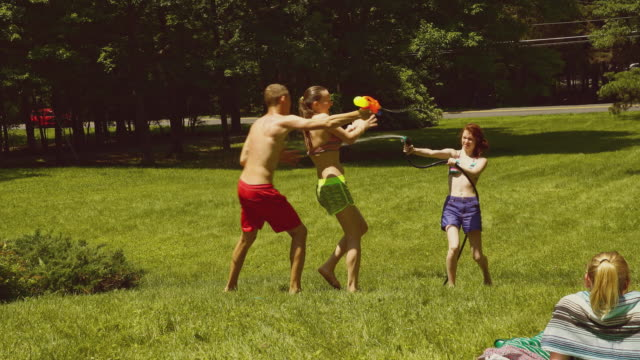 family fun at the summer's picnic: teenager girls and young man playing with water - squirt gun stock videos and b-roll footage