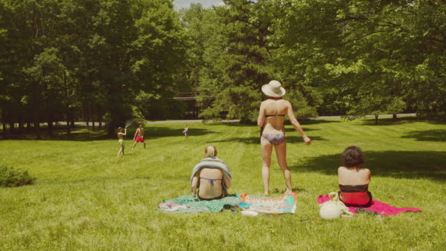 family fun at the summer's picnic: teenager girls and young man playing with water - sunbathing stock videos and b-roll footage