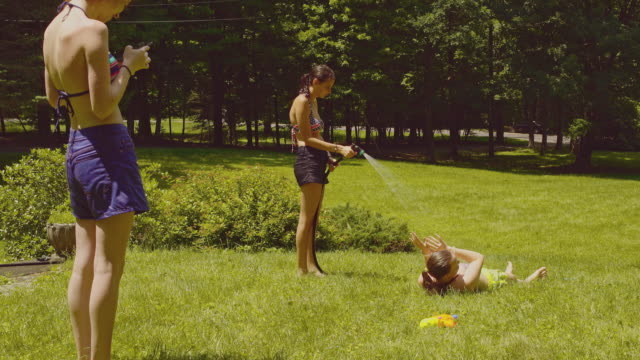 family fun at the summer's picnic: teenager girls one girl watering the other, and third filming it with the smartphone. - 14 15 years stock videos and b-roll footage