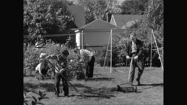 stockvideo's en b-roll-footage met ws family gardening in backyard together / united states - 1940
