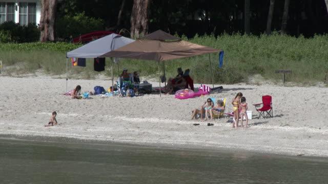 vídeos de stock, filmes e b-roll de family gathering on the beach, gulf coast florida, children playing in the sand - chapéu de sol