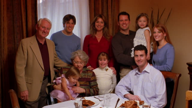 A family gathers at the dining room table for Thanksgiving dinner.