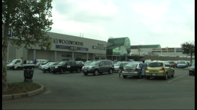 vídeos de stock, filmes e b-roll de a family gets into a car in the parking lot of woolworths. - woolworths