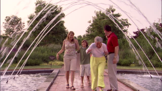 a family gets wet as they walk under an arcing water fountain. - wet wet wet stock videos & royalty-free footage