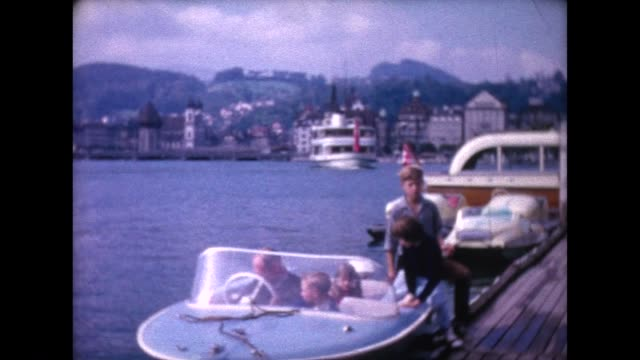 1966 family getting in small boat on lake lucerne and pulling away - lake lucerne stock videos & royalty-free footage