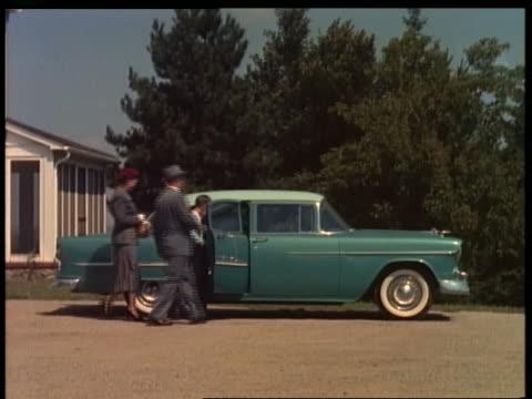 1955 family getting into blue chevrolet bel air in driveway - シボレー点の映像素材/bロール