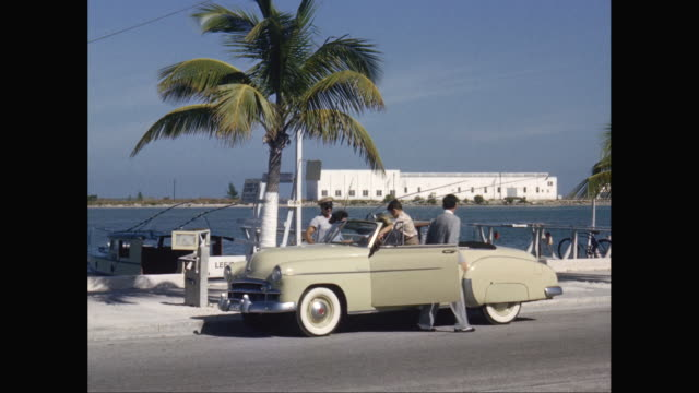 WS Family getting out from 1950s Chevrolet car at marina / United States