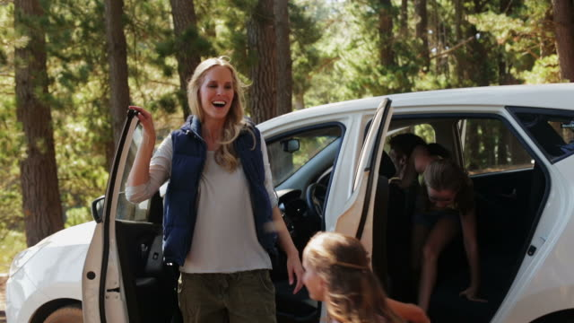 ms family getting out of car in forest and hugging - sports utility vehicle stock-videos und b-roll-filmmaterial