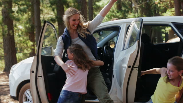 ms family getting out of car in forest and hugging - attività del fine settimana video stock e b–roll