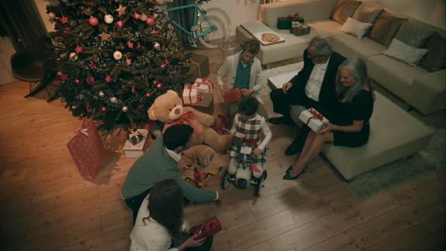 famiglia regali ogni altro presenta - regalo di natale video stock e b–roll