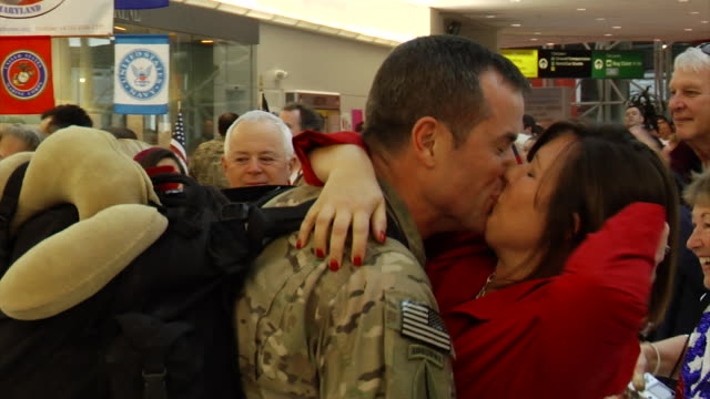 family greets soldier returning home from war on march 21, 2012 in baltimore, md - ホームカミング点の映像素材/bロール