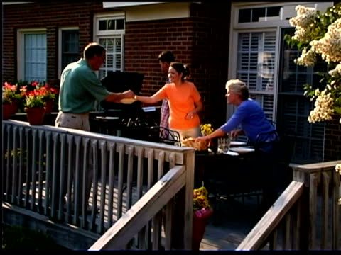 family grilling outdoors on porch - terrazza in legno video stock e b–roll