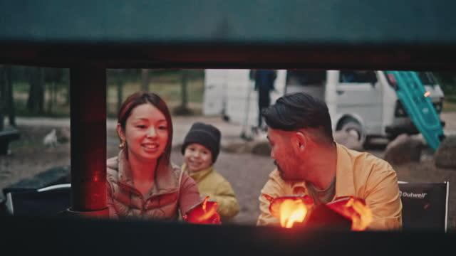 stockvideo's en b-roll-footage met familie die worsten op kampvuur tijdens wegreis grillt - surfbord