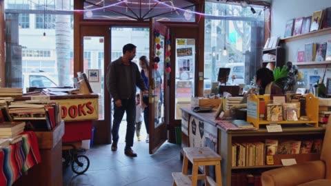 vidéos et rushes de groupe familial entrant dans la librairie - entrée
