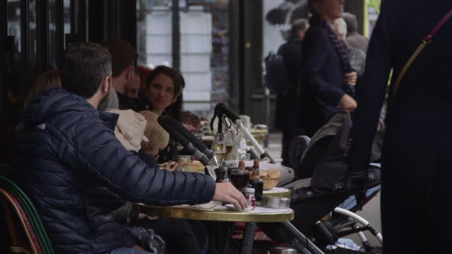 a family group sits together outside a brasserie in saintgermaindesprés paris france rushes taken from bbccom/culture absa734n - patio stock videos & royalty-free footage