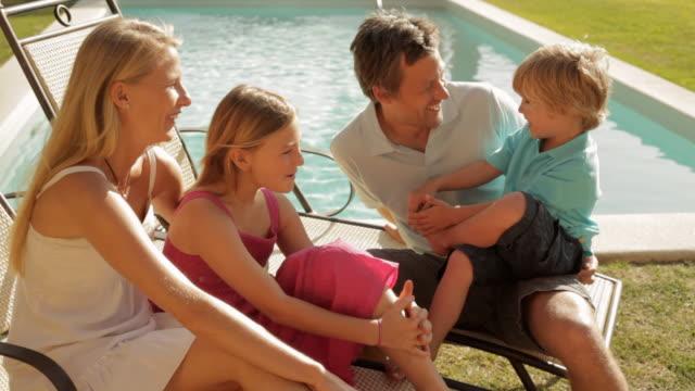 vídeos y material grabado en eventos de stock de family group sitting by pool - three quarter length