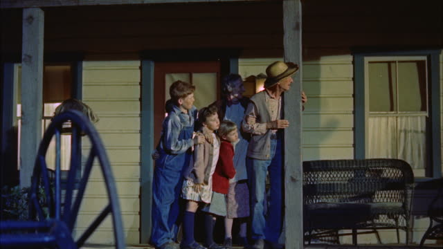 vidéos et rushes de ms pan  family group standing  on farmhouse porch and watching ku klux klan men burning barn - 1950 1959